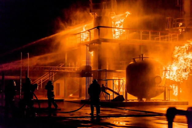 Firemen using water from hose for fire fighting at firefight training of insurance group Premium Photo