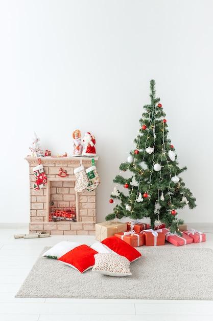 暖炉とリビングルームにプレゼントとクリスマスツリー Premium写真