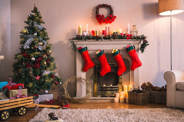 Fireplace with red socks hanging and a christmas tree Free Photo