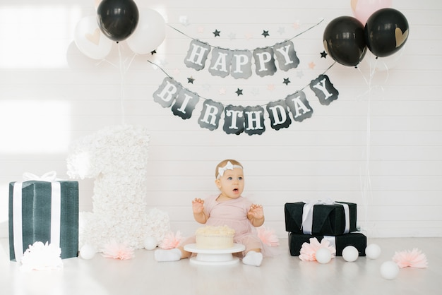 The first cake on one year birth girls. birthday party decoration in black and white. the child tastes the sweetness. happy birthday Premium Photo