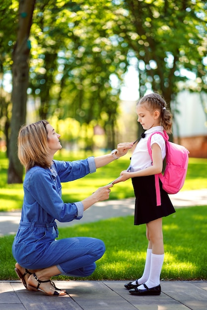 First day at school. mother leads a little child school girl in first grade Premium Photo