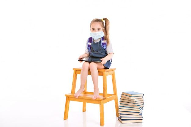 医療用マスクの1年生は、読むことを学びます。家庭用遠隔学習の小さな女の子。医療マスクの子は、ノートパソコンと本で動作します。宿題をやって。 Premium写真