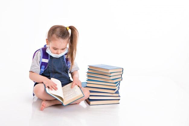 一年生は読むことを学びます。家庭用遠隔学習の小さな女の子。医療マスクの子は本を読みます。学生は宿題をしています。 Premium写真