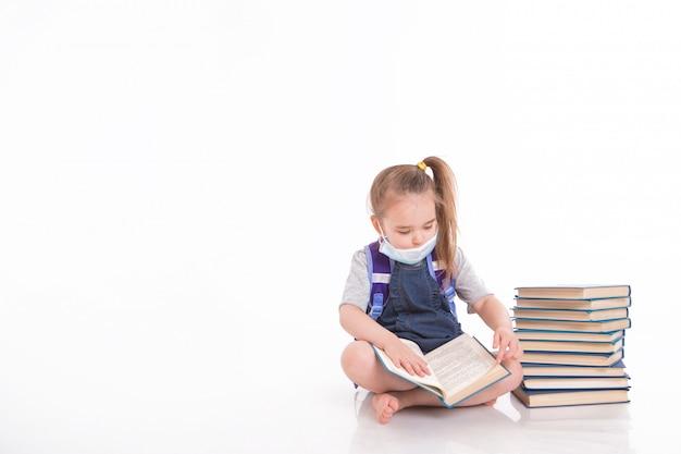 一年生は読むことを学びます。家庭用遠隔学習の小さな女の子。医療マスクの子は本を読みます。 Premium写真