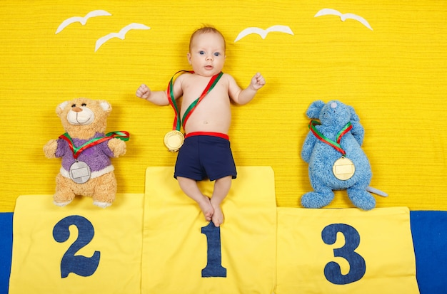 First place winner. boy is standing on a place podium in first place. Premium Photo
