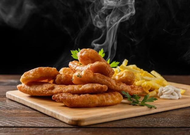 Рыба с жареным картофелем на разделочной доске с паром Premium Фотографии