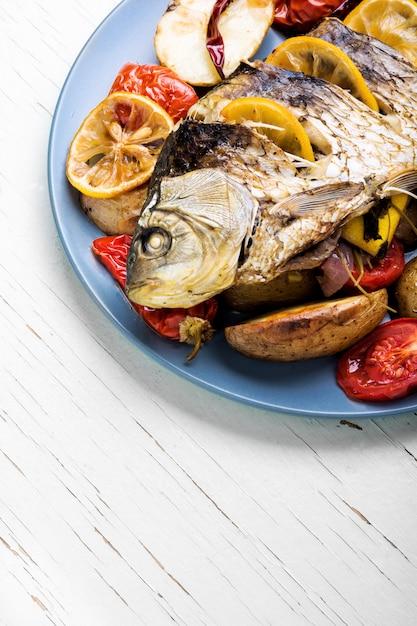 Fish baked with vegetable garnish Premium Photo