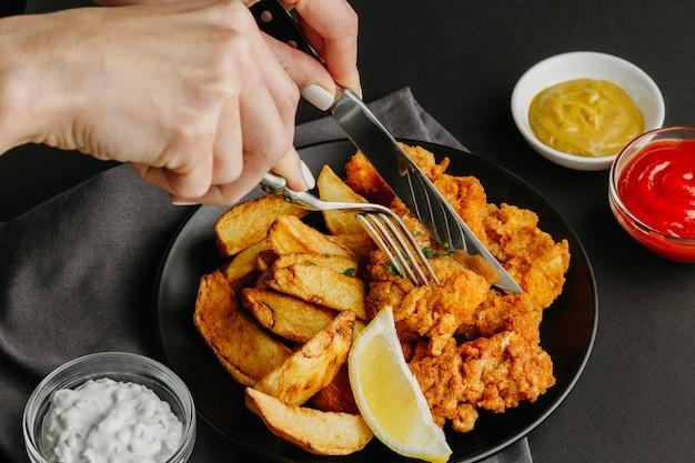 Pesce e patatine fritte sulla piastra con fetta di limone e donna con posate Foto Gratuite