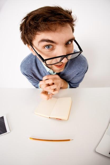 Снимок под большим углом зрения забавного молодого мужчины, сидящего за офисным столом, надевает очки, задумчиво смотрит и интересуется, создает новый контент, записывает идеи в блокнот Бесплатные Фотографии