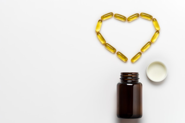 Fish oil capsule is arranged into the heart shape on white background. Premium Photo