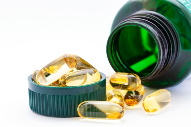 Fish oil capsules and container on white background Premium Photo