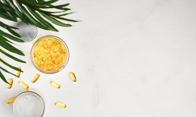 Capsule di olio di pesce con omega 3 e vitamina d in un barattolo di vetro su una superficie di cemento bianco Foto Gratuite