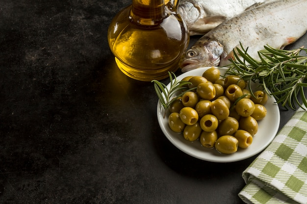 Fish olive oil and olives on dark surface photo free for Frying fish in olive oil