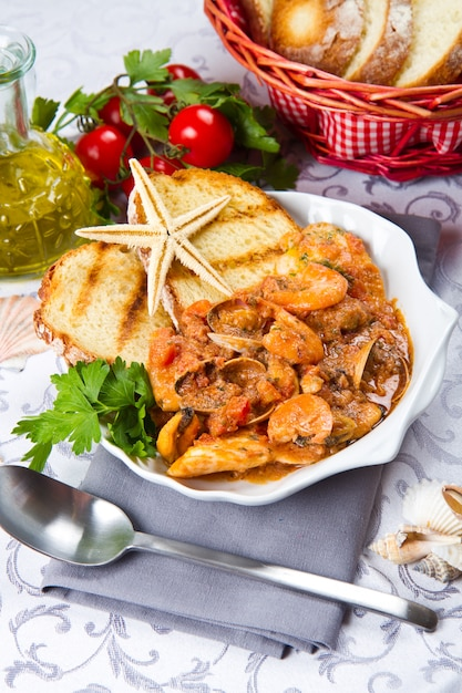 Fish soup with grilled btread on crock pot Premium Photo