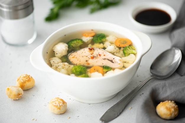 Fish soup with pink salmon, cauliflower and broccoli in a white bowl Premium Photo