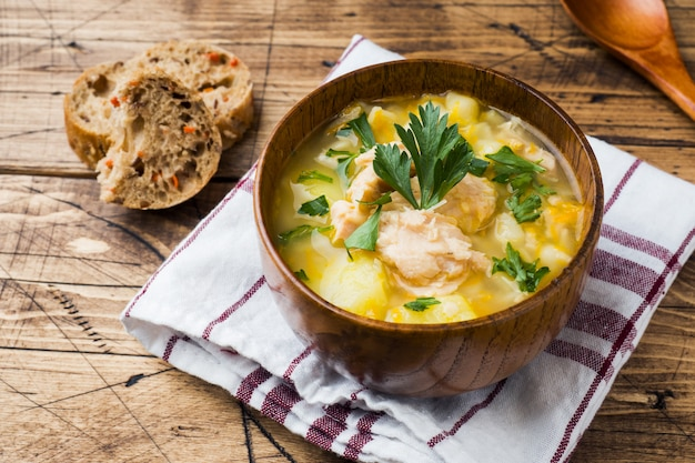 Fish soup in a wooden bowl with fresh herbs. Premium Photo