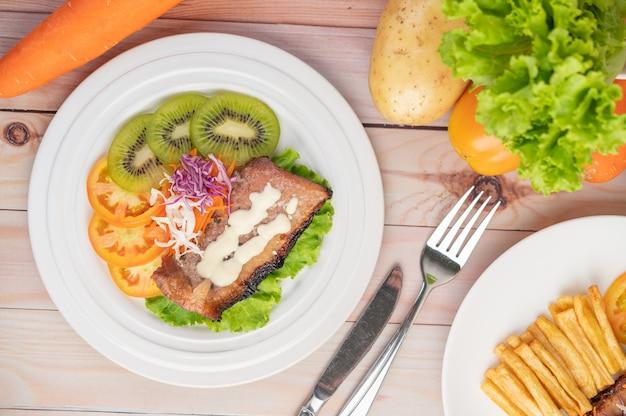 Стейк из рыбы с картофелем фри, киви, листьями салата, морковью, помидорами и капустой в белом блюде. Бесплатные Фотографии