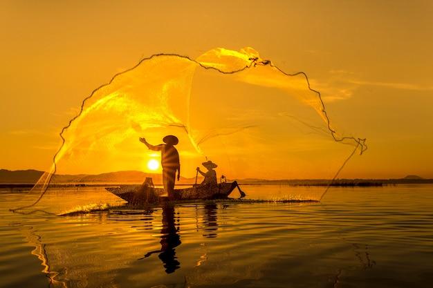 Fisherman of bangpra lake in action when fishing thailand. Premium Photo