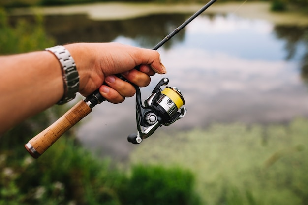 Fisherman's hand holding fishing rod at outdoors Free Photo