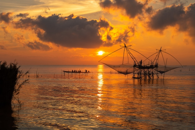Fisherman on square dip net and tourism boat at pakora village, phatthalung province, thailand Premium Photo