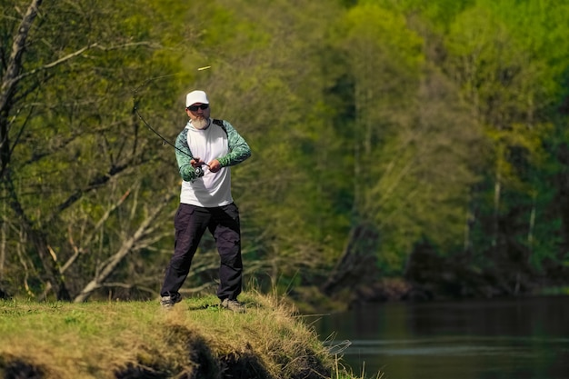 Fisherman throwing the bait into river standing on river bank Premium Photo