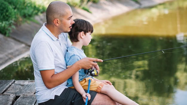 Fisherman with his son fishing on lake Free Photo