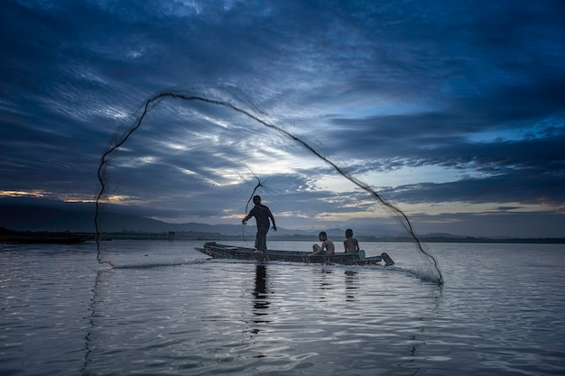 Fishermen casting are going out to fish early in the morning with wooden boats, old lanterns and nets. concept fisherman's life style. Premium Photo