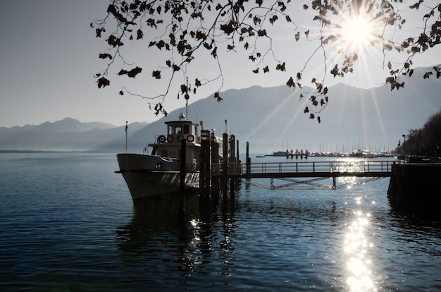 Barca da pesca su un lago alpino con splendidi raggi di sole in svizzera Foto Gratuite