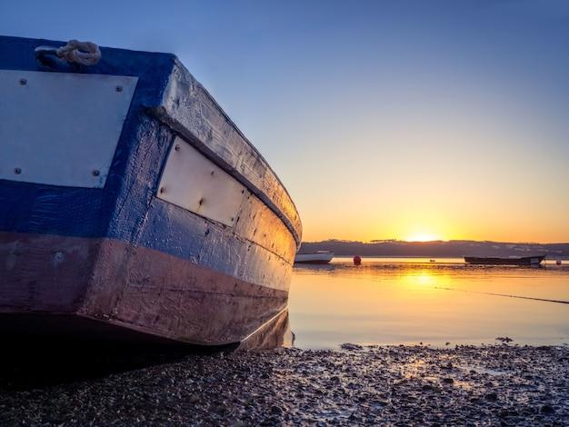 美しい夕日と川で釣りボート 無料写真