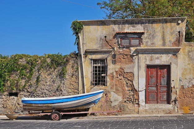 A fishing boat on a cart near the old house. rhodes, greece Premium Photo
