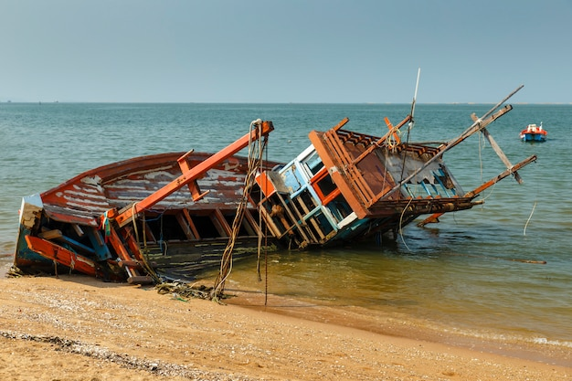 Fishing boat crashed lies on its side near the shore Premium Photo