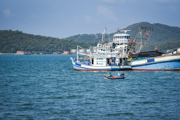 Fishing boat at harbor in the ocean sea and mountain in thailand Premium Photo