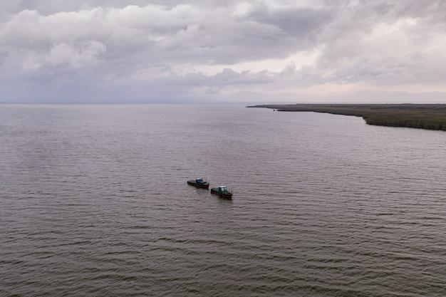 Рыбацкие лодки, плавание в спокойной воде и рыбалка под небом с облаками Бесплатные Фотографии