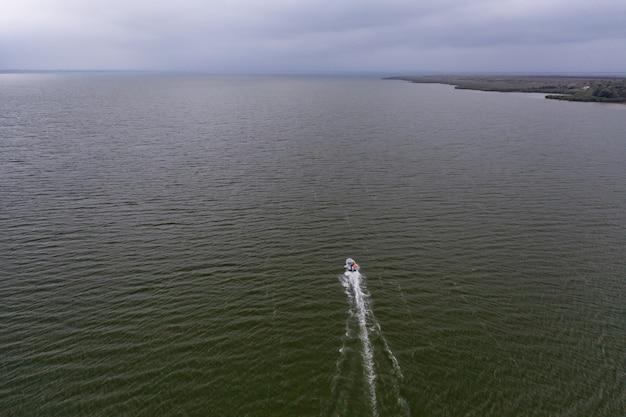 穏やかな海に浮かぶ漁船、雲のある空の下で釣りに行く 無料写真