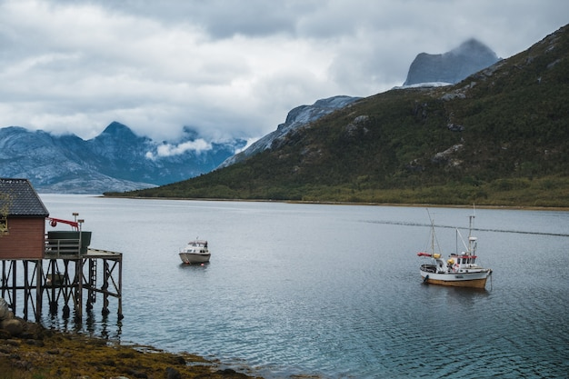 Fishing boats sailing in the lake near the mountains under the cloudy sky Free Photo