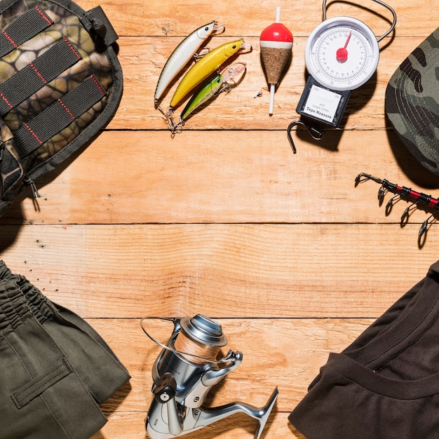 Fishing equipment and male clothing on wooden plank Free Photo