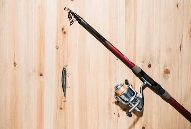 Fishing lure on the fishing rod over the wooden surface Free Photo