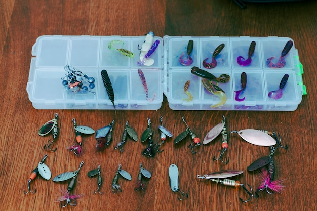 Fishing lures with boxes on wooden desk Free Photo