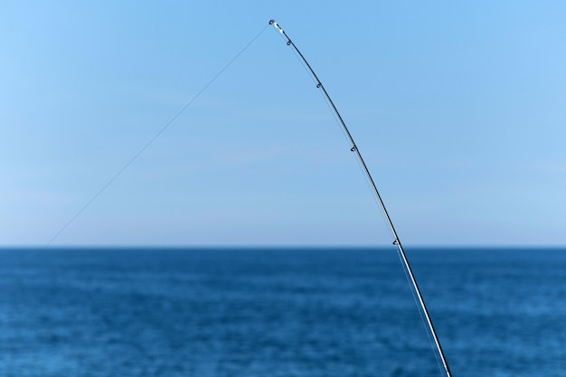 Fishing rod against blue ocean or sea background Premium Photo