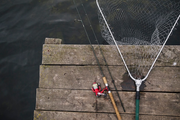 Fishing rod and fishing net on the edge of wooden pier over the lake Free Photo