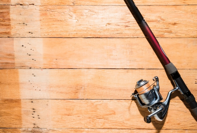 Fishing rod and fishing reel on wooden backdrop Free Photo