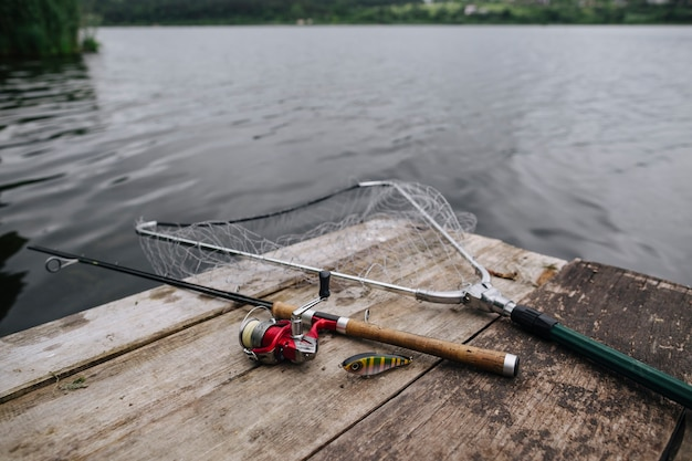 Fishing rod with lure and net on wooden pier over idyllic lake Free Photo