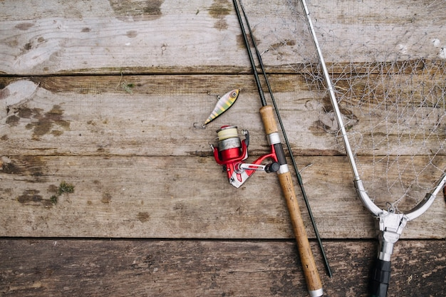 Fishing rod with lure and net on wooden pier Free Photo