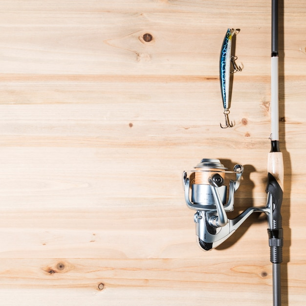 Fishing rod with lure on wooden plank Free Photo