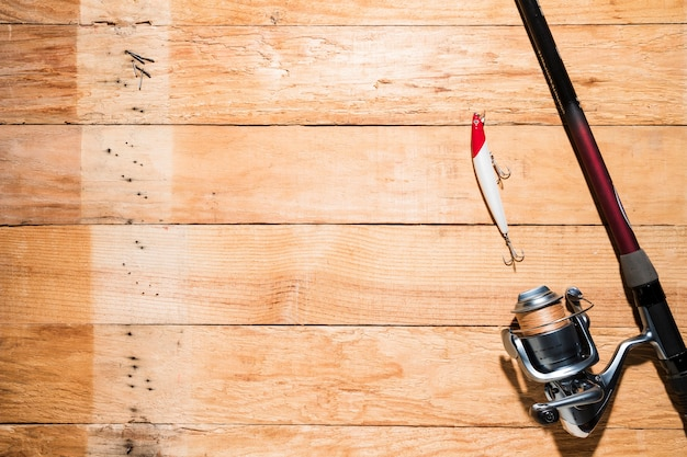 Fishing rod with red and white fishing bait on wooden plank Free Photo