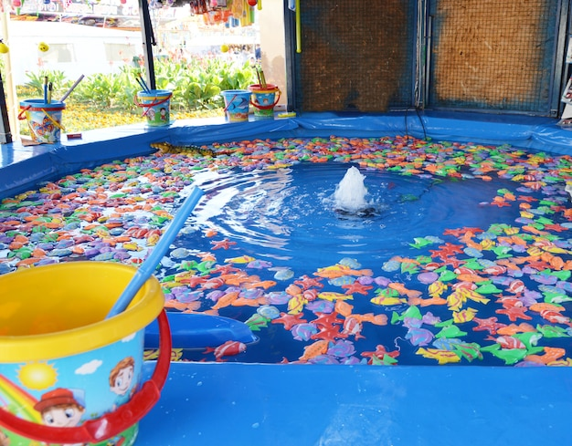 Fishing toy fish entertainment on a children's attraction in the park Premium Photo