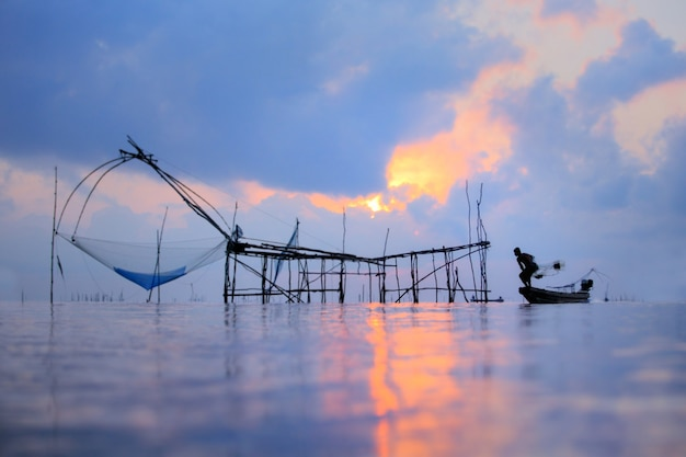 Рыболовы на шлюпке удя с fishnet, старым традиционным оборудованием тайского рыболовства. сцена силуэта в деревне pak pra, провинции pattalung, таиланде. Premium Фотографии