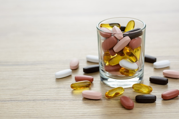 Fishoil capsules and multivitamin supplements in the small glass on the wooden table with copy space. Premium Photo