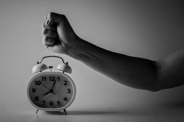 Fist is smashing for destroy a alarm clock. fight and time limits concept. Premium Photo