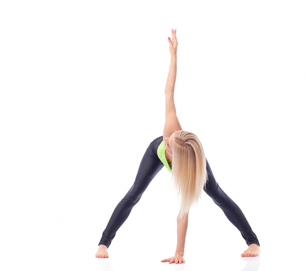Fit and active young woman performing back stretching doing yoga asana Free Photo